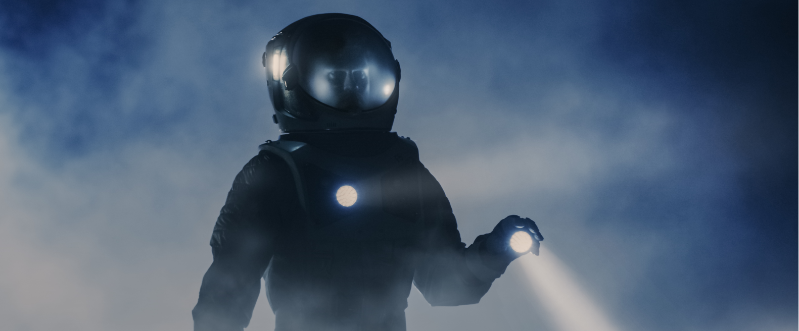 person in dark space suit searching through the fog with bright lights