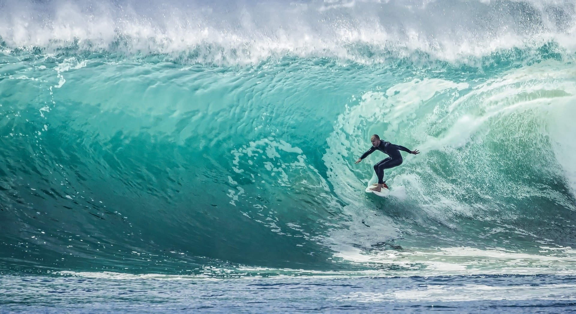 surfer riding pipeline in a large wave